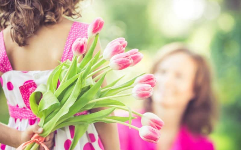 daughter holding pink flowers for christian mother on mother's day
