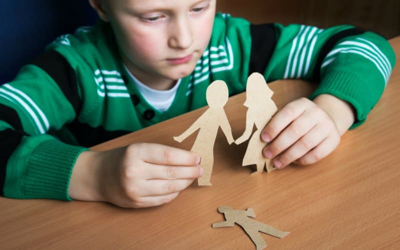 boy playing with paper family