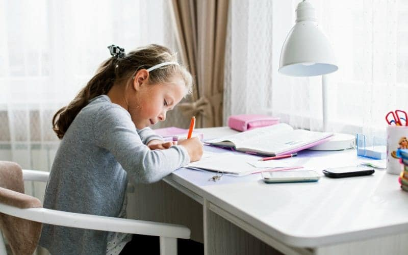 girl doing school at home