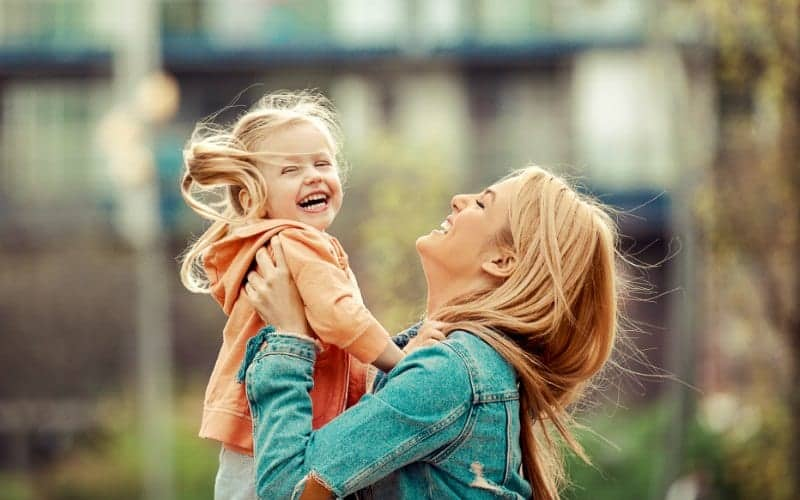 mom holding child in arms and smiling about having no child behavior problem