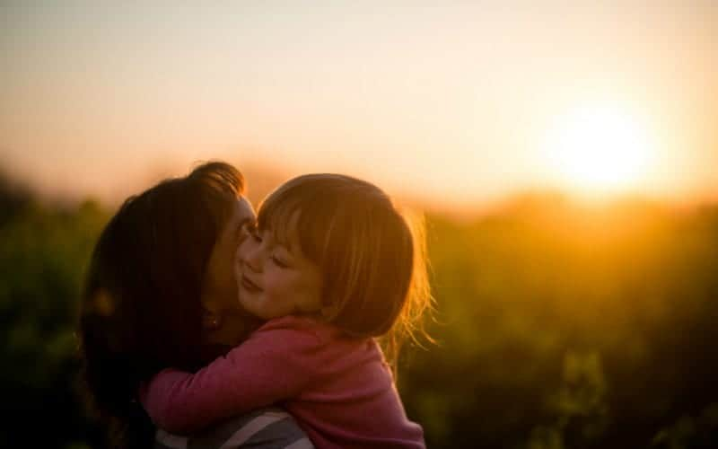 a mother hugging her toddler in the sunset, family rules make loving families