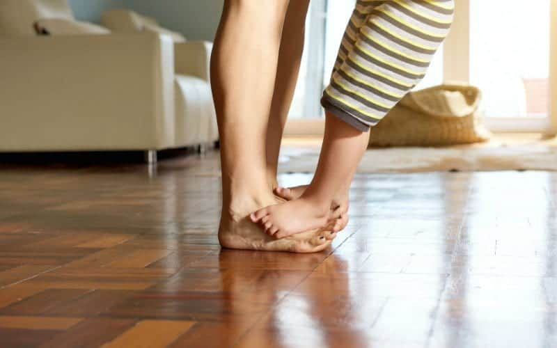 son in pajamas stepping on moms toes in the living room