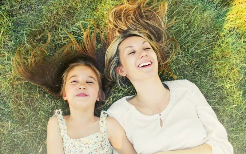 mom and daughter outside in the grass