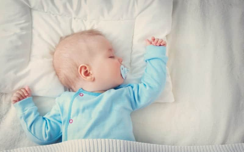 infant in blue sleeping with a pacifier