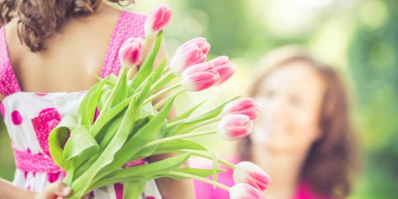 girl holding pink flower for her mother on mother's day