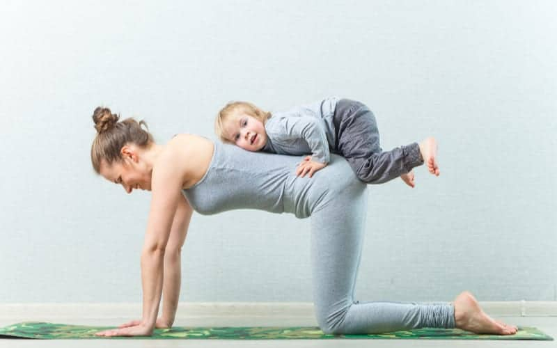 mom working out with child on her back