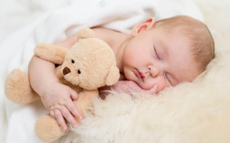 Baby resting on soft bed with sheepskin and a teddy bear for baby sleep tips