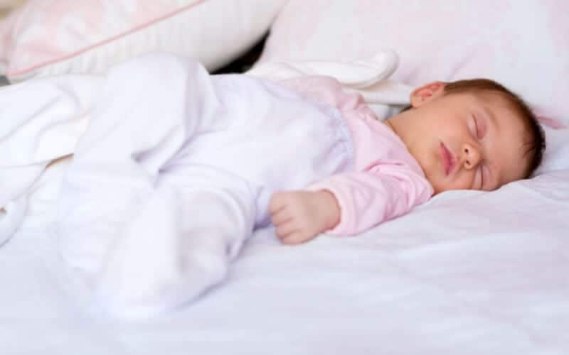 Baby sleeping on white bed with pink onesie and white pajamas.