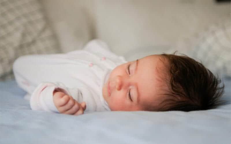 Baby sleeping on bed with dark hair and light blue sheets and white onesie.