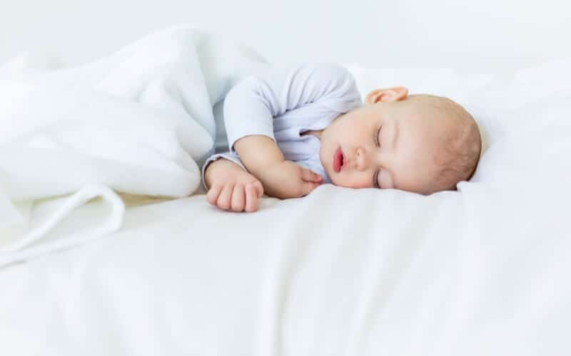 White bed with baby sleeping on it in light blue onesie.