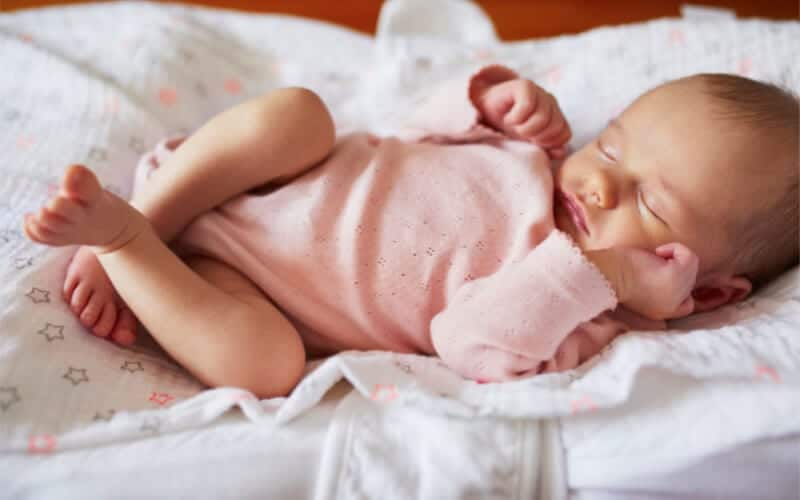 Baby sleeping on bed on a blanket with a pink onesie.