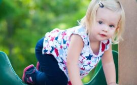 Parenting toddlers isn't for the faint of heart. Blonde toddler girl on play equipment.
