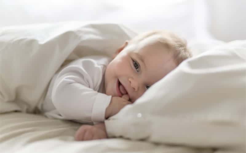 happy smiling 5 month old baby with finger in his mouth lying under a duvet cover on bed