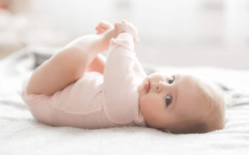 precious 5 month old baby in pink onesie lying on flat bed holding hands looking with blue eyes at the camera