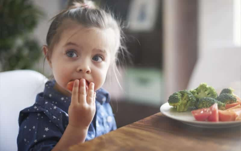child eating healthy options at lunch, not a picky eater this toddler