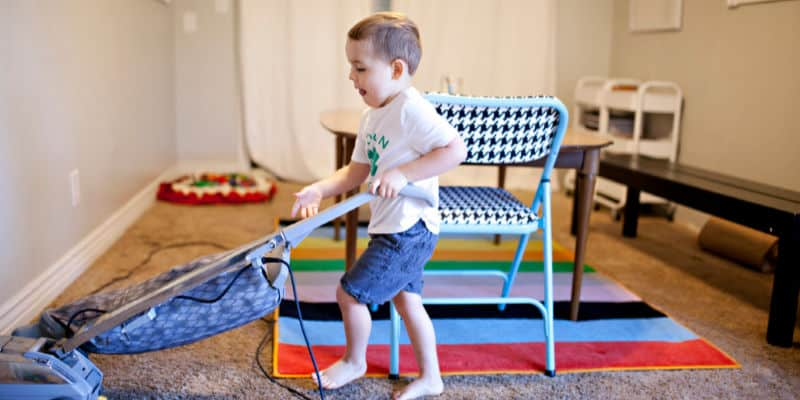 preschooler vacuuming in the living room