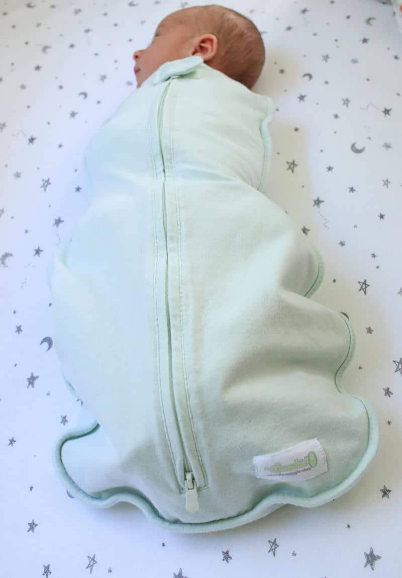 Baby in green newborn woombie swaddle that zips from the bottom