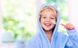 4 year old in blue robe brushing teeth