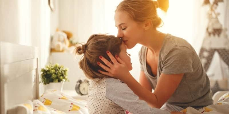 stay at home mom kissing daughter