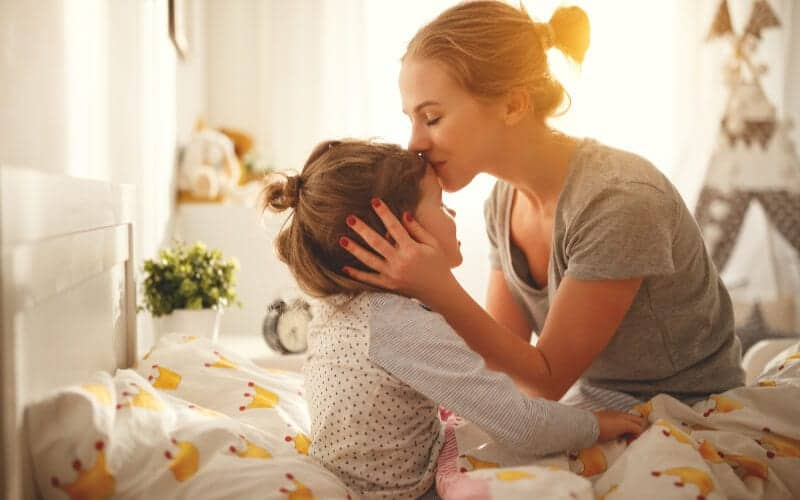 a stay at home mom kissing daughter