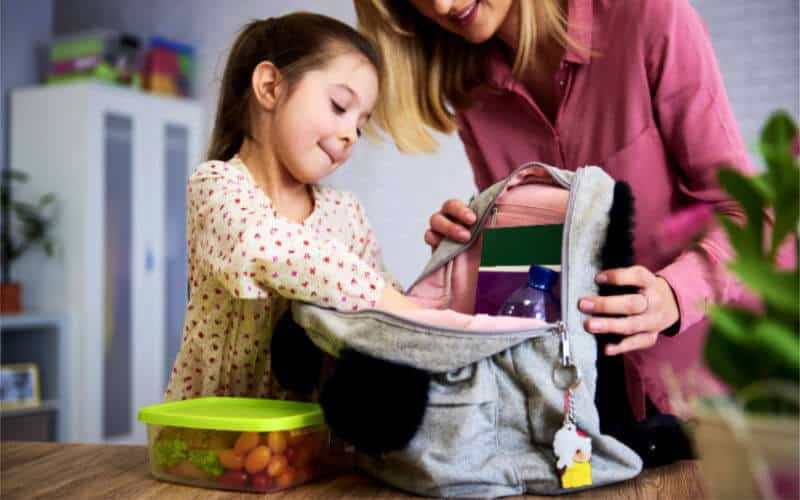 child getting ready for school with backpack