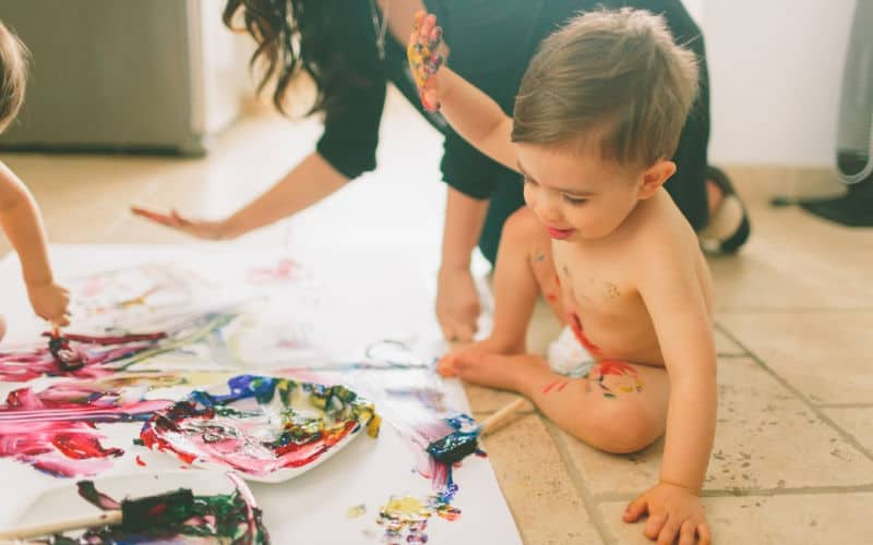 screen free activity toddler is painting on floor with mom at home