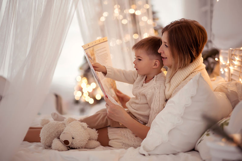 mother reading childrens book to toddler