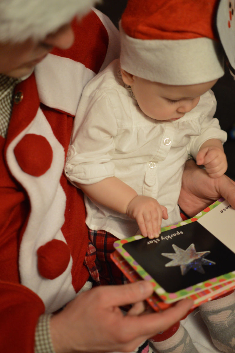 parent reading christmas book to baby in santa hat