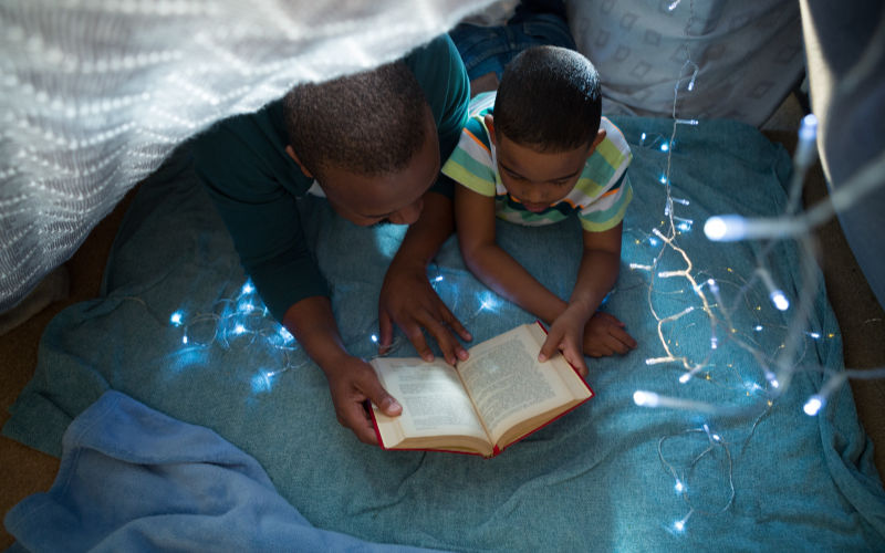 father reading book to son at bedtime under twinkle lights