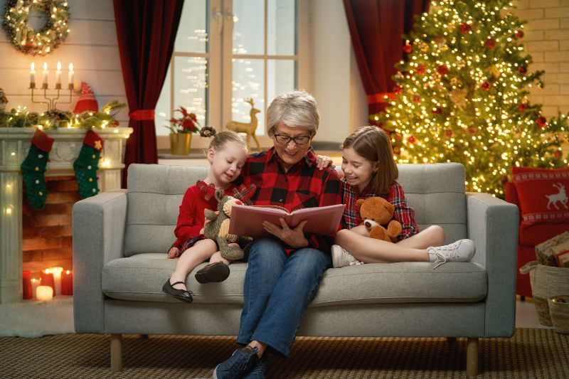 grandmother reading book to her granddaughters near Christmas tree