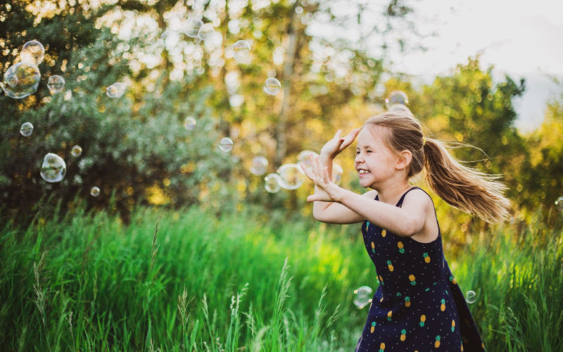 preschooler running around outside playing games with bubbles