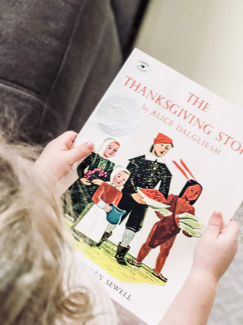 toddler reading a book about the thanksgiving story for kids