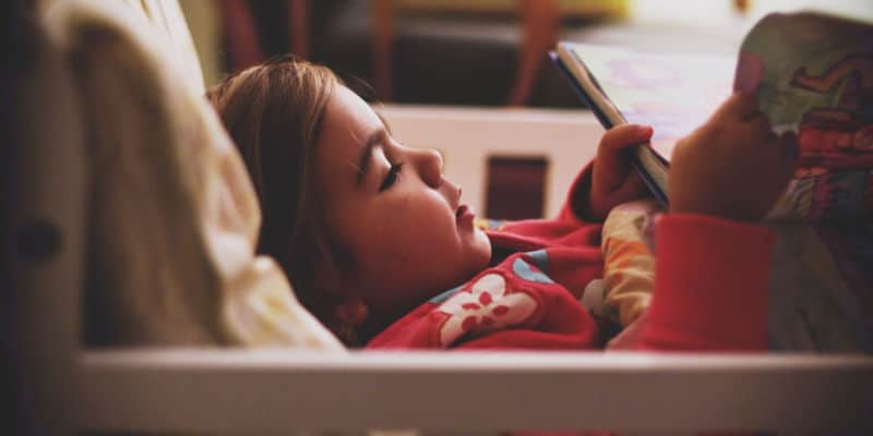 little girl in bed reading book at bedtime