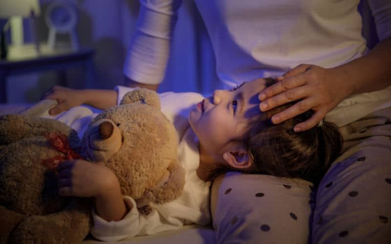 mom putting son to bed at bedtime with teddy bear
