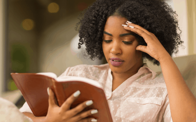 A lady is reading a devotional book from the best christian books for women's collection.