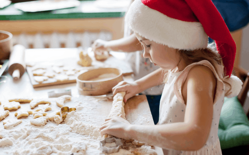 Young girl is baking cookies from her Christmas Eve Box.