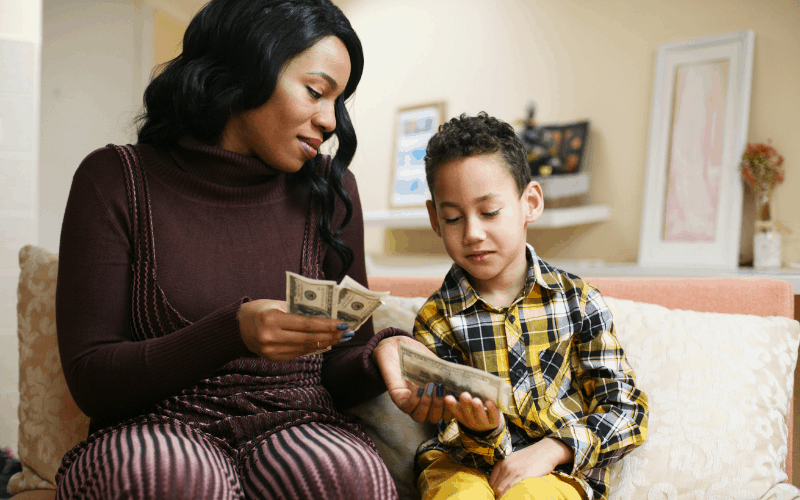 Mom is handing boy money that she has taught him to earn.