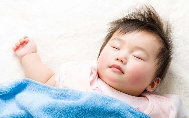 teaching baby to sleep on white bed