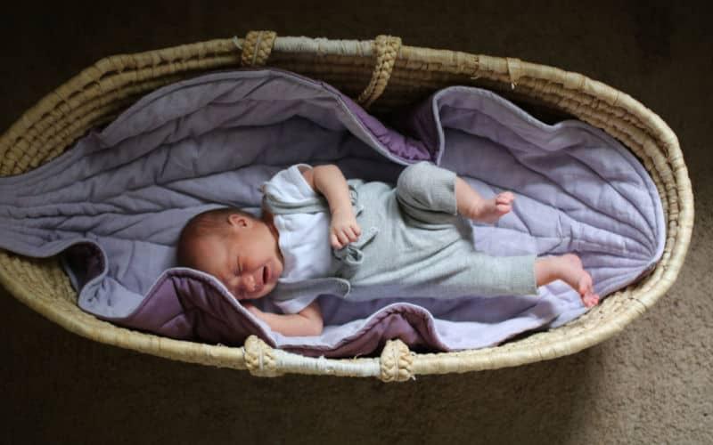 baby sleeping in old wicker basket