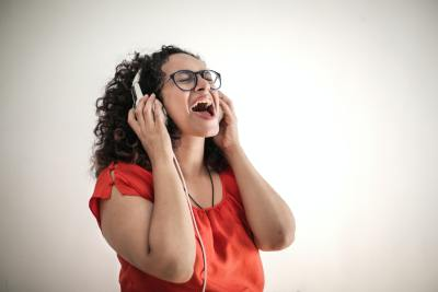 A girl wearing headphones having her own solo karaoke night