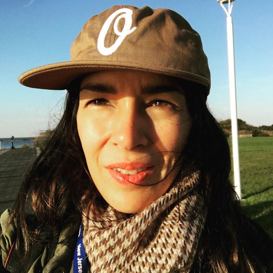 Latinx Mujer en gorra marrón con O, pelo largo negro, en bufanda. Fondo de puerto.