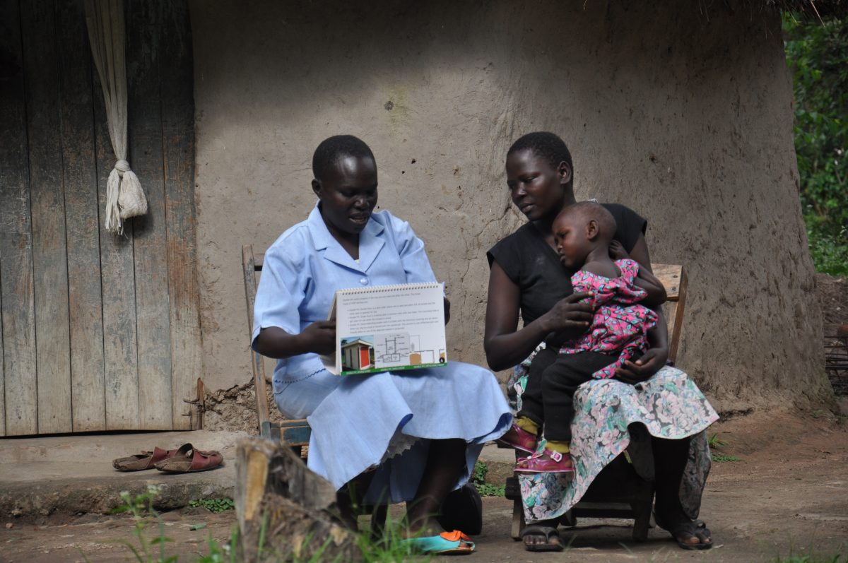Mary Kakita giving health talk to a community member during households visit