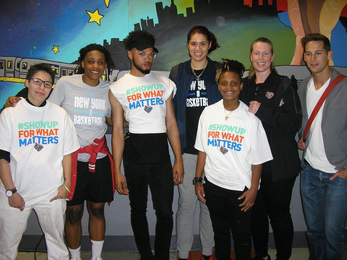 Liberty players Shavonte Zellous and Amanda Zahui B and assistant coach Katie Smith with volunteers and staff at the Ali Forney Center in Harlem (239708)