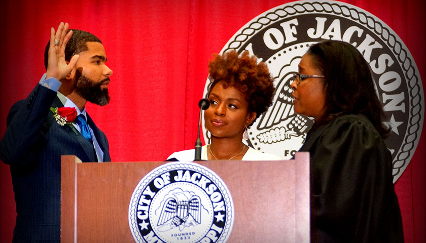Chokwe Antar Lumumba (left) is sworn-in, becoming Jackson's youngest mayor. Court of Appeals Judge Latrice Westbrooks right) administers the oath of office to Lumumba as his wife Ebony looks on. (246503)