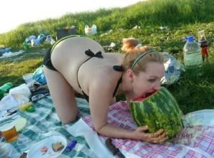 Russian woman in bikini eating a watermelon