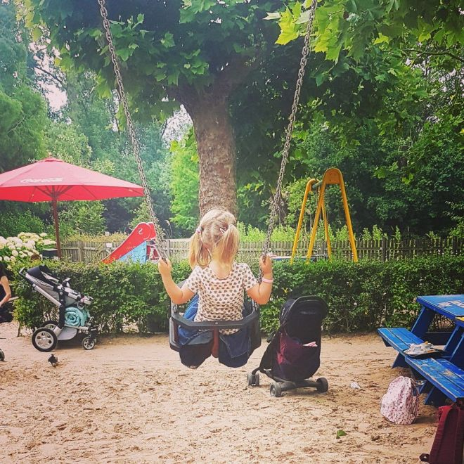 Child on a swing at the Groot Melkhuis in the Vondelpark Amsterdam