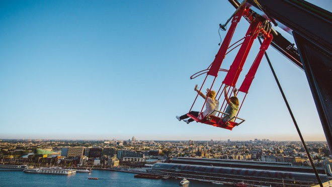 """Teenagers swinging out over Amsterdam - Swing """"Over the Edge"""" at the A'DAM Lookout"""