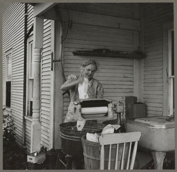 Farm woman washing clothes in her motor-driven washing machine. Near Lincoln, Vermont taken by Louise Rosskam. 1940. Library of Congress