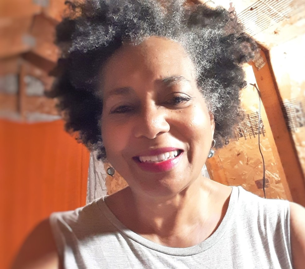 Black woman with natural hair and wearing a gray shirt smiling