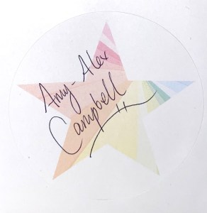 A faded AAC Publishing star logo printed on a round white sticker, and Amy-Alex Campbell's signature scrawled across the top.